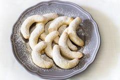 Tyska julbakelser: växande vanillekipferl för vanilj på grå färgplattan Vit handdukbakgrund Top beskådar Julfilial och klockor Arkivbild