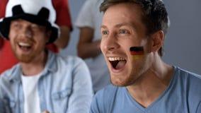 Tyska supportrar som firar seger av landslaget, hållande ögonen på match i bar royaltyfri fotografi