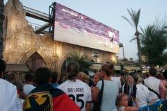 Tyskfans som håller ögonen på fotbollsmatchen på jätte- tv Arkivfoton