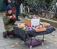 TYSKLAND FRANKFURT: 12 DECEMBER 2016 - flickan sitter på gatan och att sticka tillverkar och säljer dem Fotografering för Bildbyråer