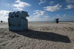 Tyskland Norddeich, Greetsiel, med huva strandstol på stranden royaltyfri fotografi