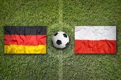 Tyskland vs Polen flaggor på fotbollfält Royaltyfri Fotografi