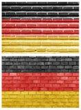 Tysklandflagga på olika tegelstenväggar Arkivfoto