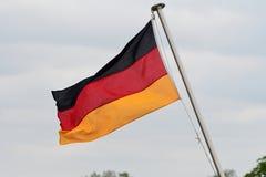 Tysklandflagga som bl?ser i vinden arkivfoton