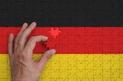 Tysklandflaggan visas på ett pussel, som handen för man` s avslutar för att vika royaltyfri bild