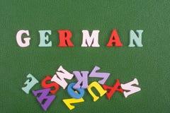 Tyskt ord på grön bakgrund som komponeras från träbokstäver för färgrikt abc-alfabetkvarter, kopieringsutrymme för annonstext Arkivfoto