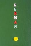 Tyskt ord på grön bakgrund som komponeras från träbokstäver för färgrikt abc-alfabetkvarter, kopieringsutrymme för annonstext Arkivbilder