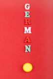 Tyskt ord på röd bakgrund som komponeras från träbokstäver för färgrikt abc-alfabetkvarter, kopieringsutrymme för annonstext lära Arkivfoton