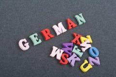 Tyskt ord på svart brädebakgrund som komponeras från träbokstäver för färgrikt abc-alfabetkvarter, kopieringsutrymme för annonste Royaltyfria Foton