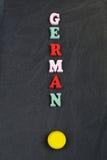 Tyskt ord på svart brädebakgrund som komponeras från träbokstäver för färgrikt abc-alfabetkvarter, kopieringsutrymme för annonste Arkivbilder