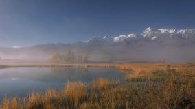 Tyst bergsjö i en dimmig morgon med glaciärer berg, höstmorgontimelapse, Sibirien, Altai arkivfilmer