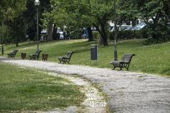 Tyst fyrkant med trädgårdbänkar och massor av gräsplan arkivfoton