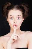 Tyst och hyssja ner Kvinna som rymmer hennes finger till hennes kanter Arkivfoto