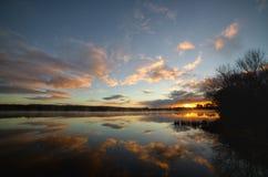 Tyst soluppgång över sjön Arkivbilder