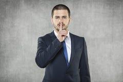 Tystnad behar, affärsmannen som gör tystnadtecknet royaltyfri bild