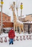 Tyumen, Russia - Boy near a sculpture of a giraffe. Winter cloudy day royalty free stock images