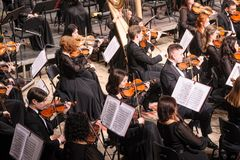 Symphony orchestra on stage. Violin group plays Royalty Free Stock Photo