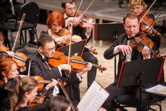 Symphony orchestra on stage. Violin group plays Stock Photo