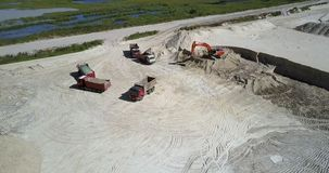 Excavator digs sand to fill tip lorries at quarry upper view