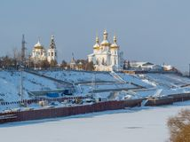 Tyumen, Russia. View of the city center of Tyumen, with white Russian orthodox churches with golden domes covered in snow and the frozen Tura River royalty free stock image