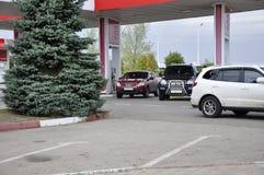 Tyumengebied, Siberië Rusland 1 augustus, 2017 Twee auto's zijn bijtanken op het van brandstof voorzien traveling stock fotografie