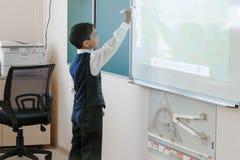 TyuSchool. Cool room. The boy in school uniform writes on an interactive whiteboard royalty free stock photos