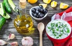 Tzatziki, ogórek, butelka oliwa z oliwek na starym drewnianym stole przeciw tłu tnąca deska Zdjęcia Stock