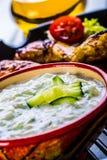 Tzatziki sås Tzatziki dressing Tzatziki dressing med grillad fega ben och ny grönsak, grönsallatblad och körsbärtomatoe Royaltyfri Bild