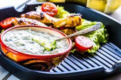 Tzatziki sås Tzatziki dressing Tzatziki dressing med grillad fega ben och ny grönsak, grönsallatblad och körsbärtomatoe Arkivfoton
