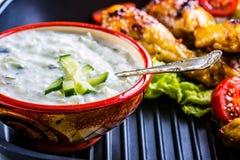 Tzatziki sås Tzatziki dressing Tzatziki dressing med grillad fega ben och ny grönsak, grönsallatblad och körsbärtomatoe Arkivfoto