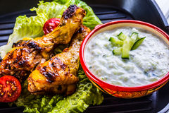 Tzatziki sauce. Tzatziki dressing. Tzatziki dressing with grilled chicken legs and fresh vegetable,lettuce leaf and cherry tomatoe Royalty Free Stock Photos
