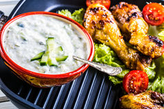 Tzatziki sauce. Tzatziki dressing. Tzatziki dressing with grilled chicken legs and fresh vegetable,lettuce leaf and cherry tomatoe Stock Images