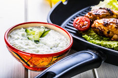 Tzatziki sauce. Tzatziki dressing. Tzatziki dressing with grilled chicken legs and fresh vegetable,lettuce leaf and cherry royalty free stock photos
