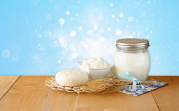 Tzfatit乳酪、村庄和牛奶在木桌上在蓝色闪烁背景 犹太假日Shavuot概念 免版税库存图片