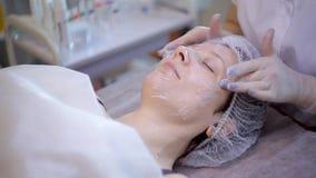 Używa twarzowe maski na twarzy kobieta w piękno salonie zbiory