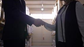 Uścisk dłoni w backlight między biznesmenem i biznesową kobietą przy magazynem zbiory