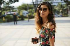 Uśmiechnięta Azjatycka kobieta patrzeje kamerę z smartphone obraz stock