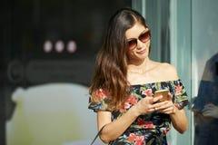 Uśmiechnięta dama używa smartphone blisko robi zakupy zdjęcia stock