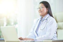 Uśmiechnięta dorosła kobieta pracuje w szpitalnym biurze fotografia stock