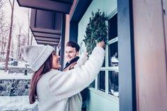 Uśmiechnięta dziewczyna jest ubranym ciepłego żakieta kładzenia wianek na dzwi wejściowy zdjęcia stock