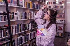 Uśmiechnięta kędzierzawa dziewczyna podnosi jej rękę w purpurowym pulowerze obrazy royalty free