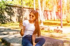 Uśmiechnięta młoda kobieta siedzi jej smartphone i używa obraz royalty free