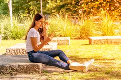 Uśmiechnięta młoda kobieta siedzi jej smartphone i używa zdjęcie stock