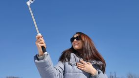 Uśmiechnięta młoda kobieta w okularach przeciwsłonecznych ono fotografuje używa smartphone i selfie kij w parku podczas pogodnego zbiory wideo