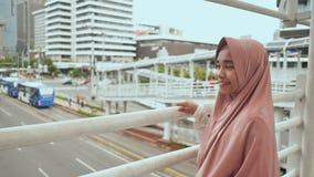 Uśmiechnięta Muzułmańska dziewczyna chodzi na przemianie nad drogowym ruchem drogowym Indonezja zbiory wideo