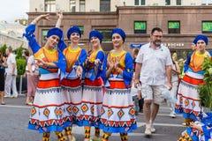 Uśmiechnięte dziewczyny w pięknych krajowych kostiumach pozuje na ulicie zdjęcia royalty free