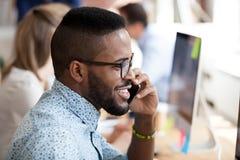 Uśmiechnięty afrykański pracownik opowiada na telefonie z klientem obraz stock