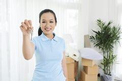 Uśmiechnięty etniczny kobieta seansu klucz nowy mieszkanie obraz royalty free