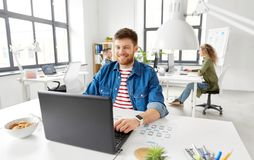 Uśmiechnięty kreatywnie mężczyzna z laptopem pracuje przy biurem zdjęcie stock