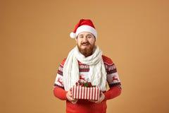Uśmiechnięty miedzianowłosy mężczyzna z brodą ubierał w pulowerze z rogaczami, białym trykotowym szaliku i kapeluszu Santa czerwo fotografia royalty free